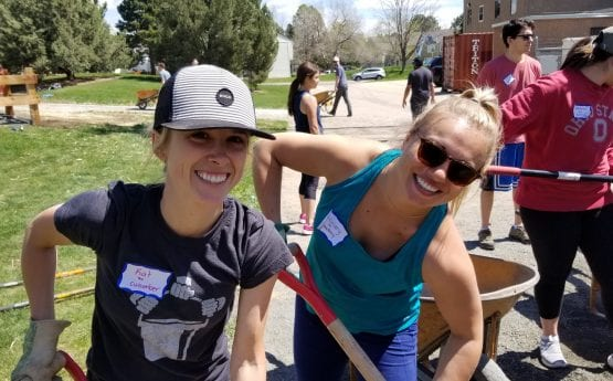 Two girls having fun shoveling mulch with Denver Urban Gardens