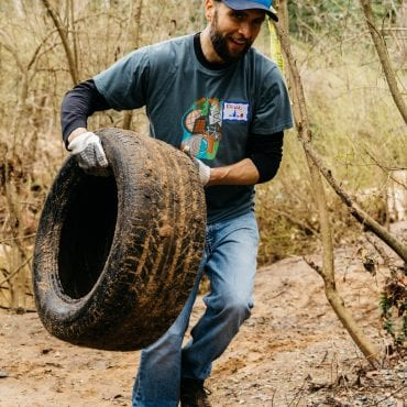 Volunteer in Atlanta removes trash from a river with Park Pride
